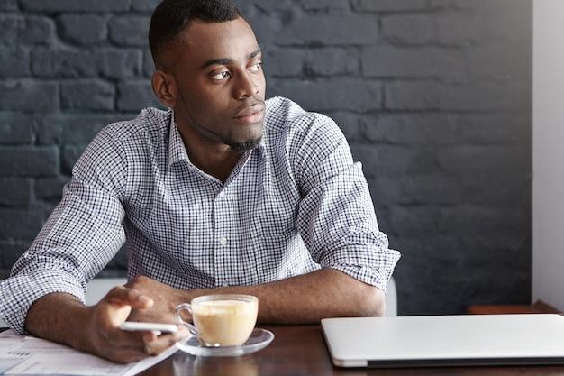 Aantrekkelijke jonge afro-amerikaanse ondernemer sms typen op slimme telefoon met doordachte en serieuze blik Gratis Foto