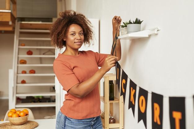 Aantrekkelijke jonge afro-amerikaanse vrouw kamer met garland versieren voor halloween-feest, kopie ruimte Premium Foto