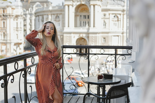 Aantrekkelijke jonge blanke vrouw gekleed in rode polka dot jurk staat op het terras bij de salontafel met uitzicht op de straat van de stad met oude architectonische gebouwen Gratis Foto