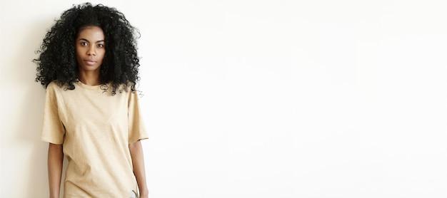 Aantrekkelijke jonge donkere vrouw met afro kapsel dragen oversized t-shirt kijken, met ernstige gezichtsuitdrukking. schattig afrikaans meisje gekleed nonchalant poseren binnenshuis op witte muur Gratis Foto