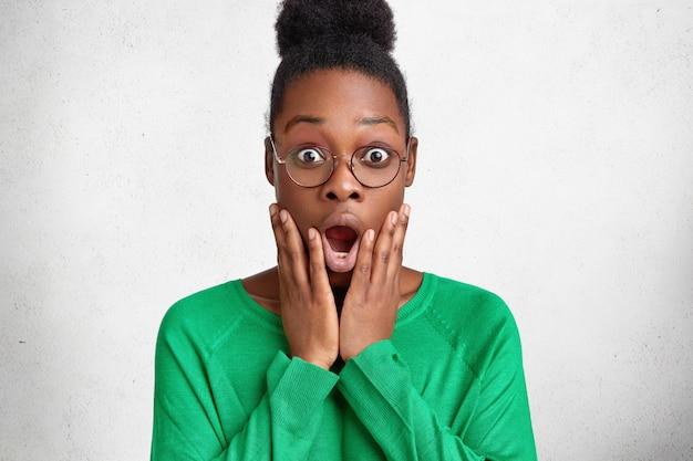 Aantrekkelijke jonge emotionele afro-amerikaanse vrouw kijkt met grote verrassing naar de camera, houdt de mond wijd open Gratis Foto