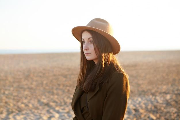 Aantrekkelijke jonge europese vrouw gekleed in stijlvolle overkleding met een mooie wandeling langs de kustlijn op zonnige dag, kwam naar de zee voor het overwegen van de zonsondergang. mooie vrouw in hoed het ontspannen op zandig strand Gratis Foto
