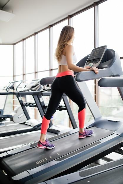 Aantrekkelijke jonge fitness model draait op een loopband, houdt zich bezig met fitness sportclub Gratis Foto