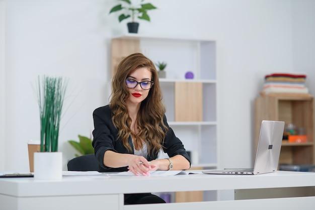 Aantrekkelijke jonge kantoorvrouw in formele kleding werkt met zakelijk papierwerk aan de balie. Premium Foto