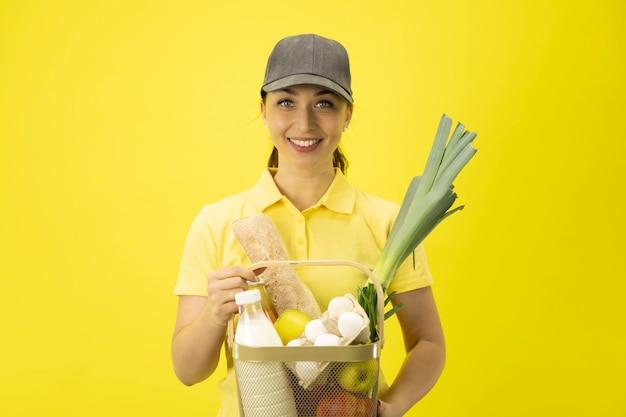 Aantrekkelijke jonge leveringsvrouw in geel uniform en de mand van de hoedenholding met producten Premium Foto