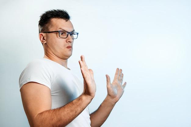 Aantrekkelijke jonge man maakt bang gebaar met palmen, verdedigt zich tegen iemand, vraagt om het onmiddellijk te stoppen. Premium Foto