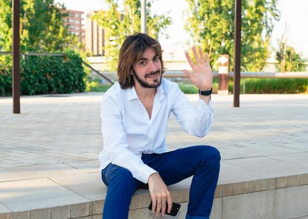 Aantrekkelijke jonge man met baard, met wit shirt heeft een smartphone in zijn hand en is in het park, glimlacht en golven Premium Foto