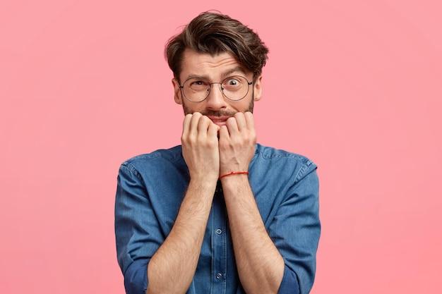 Aantrekkelijke jonge man met verwarde nerveuze uitdrukking, bijt vingernagels, maakt zich zorgen om een vreselijke fout te maken, voelt zich angstig, kijkt beschaamd, draagt spijkerblouse, geïsoleerd over roze muur Gratis Foto
