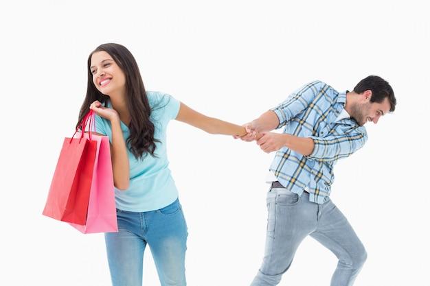 Aantrekkelijke jonge man trekt zijn shopaholic vriendin Premium Foto