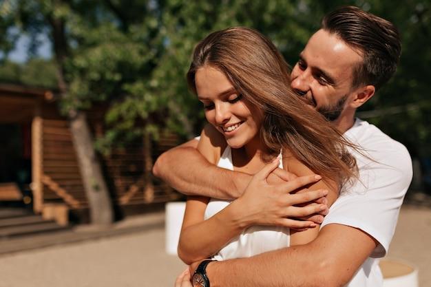 Aantrekkelijke jonge mensen knuffelen en kussen in zonlicht op het strand Gratis Foto
