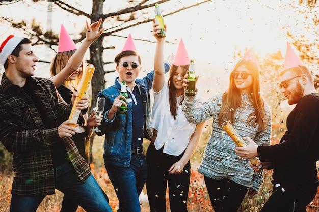 Aantrekkelijke jonge mensen verhogen glazen bier en exploderende confetti crackers tijdens de kerstviering op het platteland Premium Foto