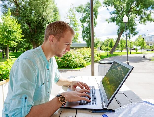 Aantrekkelijke jonge mensenstudent die laptop buiten met behulp van Premium Foto