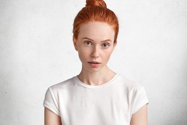 Aantrekkelijke jonge roodharige vrouw met huid met sproeten en serieuze blik, gekleed in casual wit t-shirt, modellen tegen witte betonnen muur. Gratis Foto