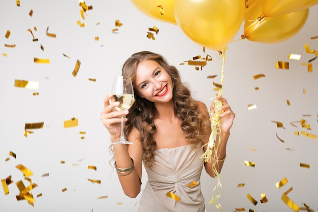 Aantrekkelijke jonge stijlvolle vrouw nieuwjaar vieren, champagne drinken met luchtballons, gouden confetti vliegen, glimlachend gelukkig, wit, geïsoleerd, feestjurk dragen Gratis Foto