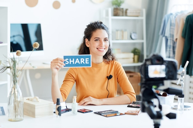 Aantrekkelijke jonge volwassen schoonheid blogger zittend aan tafel met share print teken, horizontaal portret shot Premium Foto