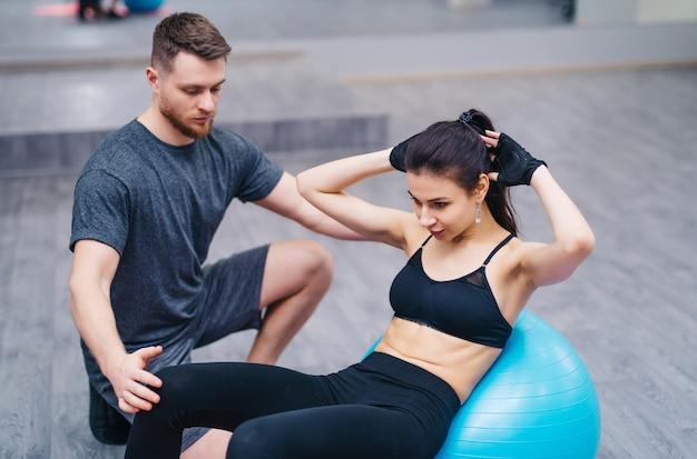 Aantrekkelijke jonge vrouw die abs op een geschiktheidsbal doet met persoonlijke trainer op de vloer in gymnastiek. Premium Foto