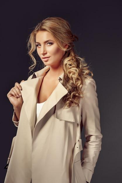 Aantrekkelijke jonge vrouw die in beige laag camera bekijkt Premium Foto