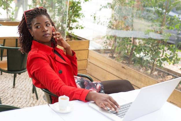 Aantrekkelijke jonge vrouw die laptop en smartphone in restaurant gebruikt Gratis Foto