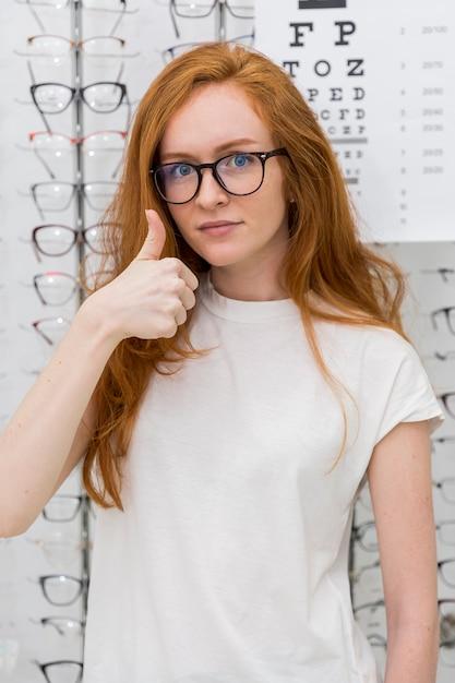 Aantrekkelijke jonge vrouw die met schouw duim op gebaar tonen die camera in opticawinkel bekijken Gratis Foto