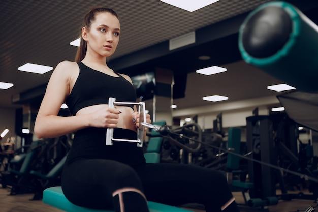 Aantrekkelijke jonge vrouw doet oefeningen voor armen en rug in een sportschool Premium Foto
