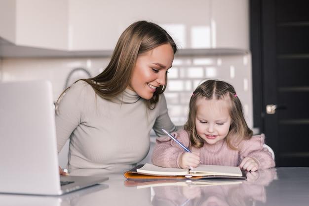 Aantrekkelijke jonge vrouw en haar kleine schattige dochter zitten aan de tafel en samen huiswerk Gratis Foto