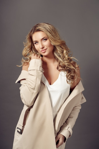 Aantrekkelijke jonge vrouw in beige jas Premium Foto
