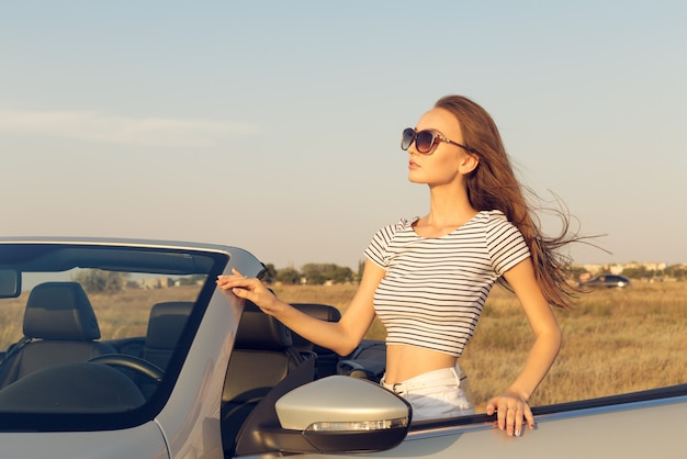 Aantrekkelijke jonge vrouw in de buurt van een converteerbare auto Premium Foto