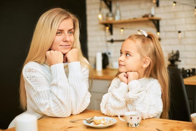 Aantrekkelijke jonge vrouw met blonde lange haren en haar mooie dochter beide in gezellige truien ontbijten in de keuken zit aan de eettafel, het drinken van thee, met cake, handen onder de kin houden Gratis Foto