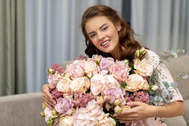Aantrekkelijke jonge vrouw met een boeket van honderden bloemen brengt tijd thuis door. Gratis Foto