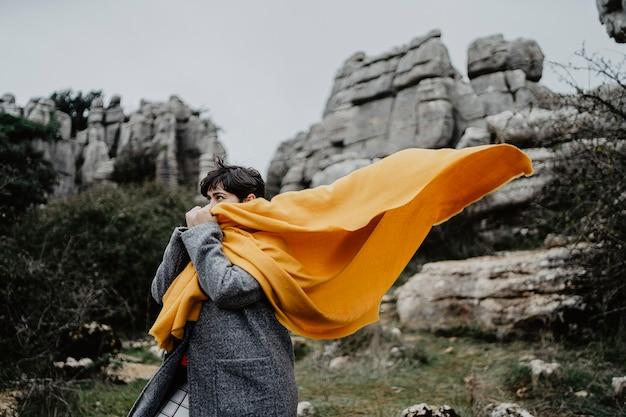 Aantrekkelijke jonge vrouw met een jas en een gele sjaal in de buurt van hoge rotswanden Gratis Foto