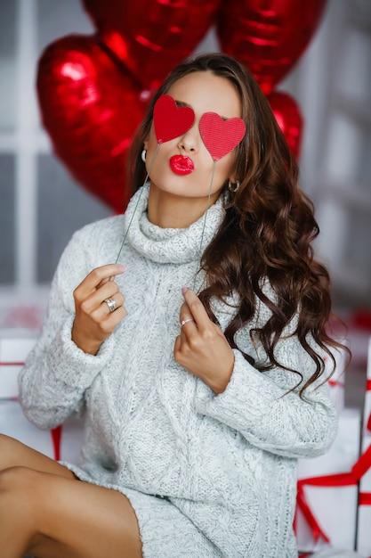 Aantrekkelijke jonge vrouw met geschenken en ballonnen Premium Foto