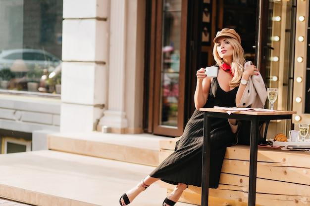 Aantrekkelijke jonge vrouw rusten na het werk in favoriete café en genieten van koffiesmaak. outdoor portret van blond meisje in stijlvolle outfit ontspannen in het weekend. Gratis Foto