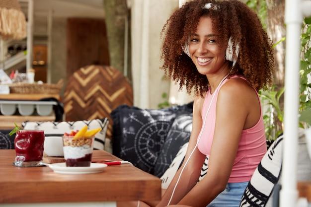 Aantrekkelijke jonge vrouw voelt zich opgewonden als favoriete liedje luistert via witte moderne hoofdtelefoonaccessoire en slimme telefoon, zit in café-interieur, omringd met heerlijke desserts. entertainment Gratis Foto