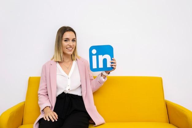 Aantrekkelijke jonge vrouw zittend op de bank holding linkedin pictogram Gratis Foto