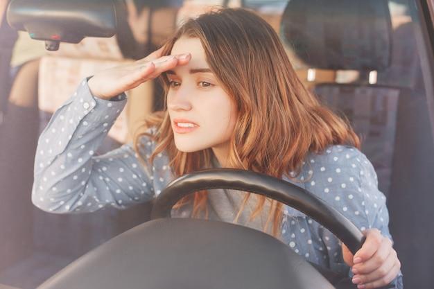 Aantrekkelijke jonge vrouwelijke bestuurder kijkt aandachtig naar de voorruit in de verte en probeert iets op de voorgrond te zien Premium Foto