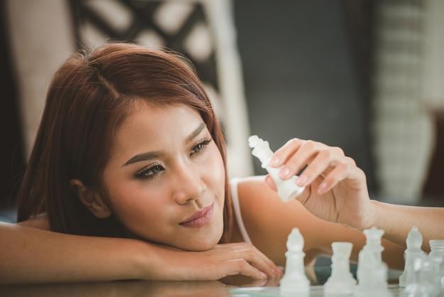 Aantrekkelijke jonge vrouwen planning in de woonkamer thuis met schaakbordspel Premium Foto