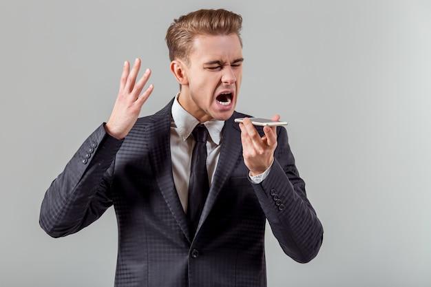 Aantrekkelijke jonge zakenman die op de telefoon spreekt. Premium Foto