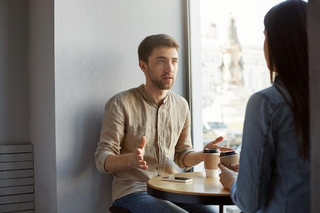 Aantrekkelijke kaukasische kerel met donker haar en varkenshaarzitting in koffie op een datum die met zijn vriendin over zijn werk spreekt, met handen gesticuleert en koffie drinkt. Gratis Foto