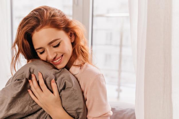 Aantrekkelijke krullende witte vrouw poseren in de ochtend. geïnteresseerd gember meisje lachen in bed. Gratis Foto
