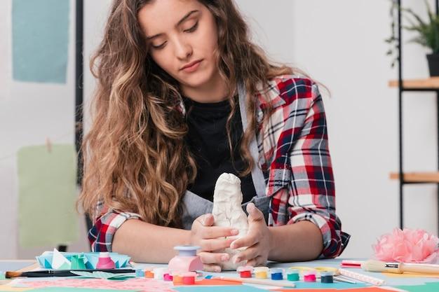 Aantrekkelijke kunstenaar die handcraftkunst maakt die witte klei gebruikt Gratis Foto