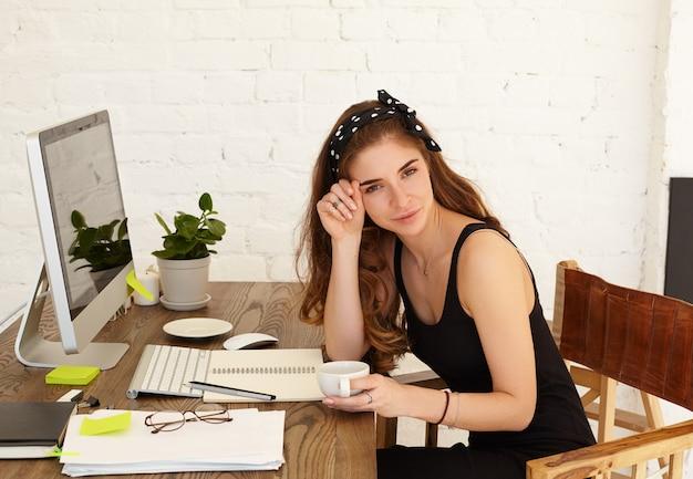 Aantrekkelijke lachende jonge vrouwelijke freelancer genieten van cappuccino tijdens de koffiepauze terwijl ze op afstand werkt in haar kantoor aan huis, met behulp van high-speed internetverbinding op de computer van het kopieerruimte scherm Gratis Foto