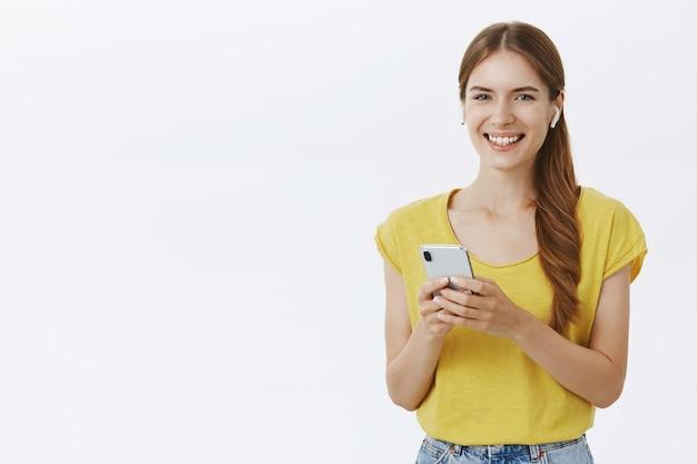 Aantrekkelijke lachende vrouw in koptelefoon luisteren muziek of podcast, met behulp van smartphone Gratis Foto