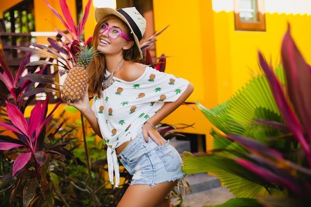 Aantrekkelijke lachende vrouw op vakantie in gedrukte t-shirt strooien hoed zomer mode, handen met ananas Gratis Foto