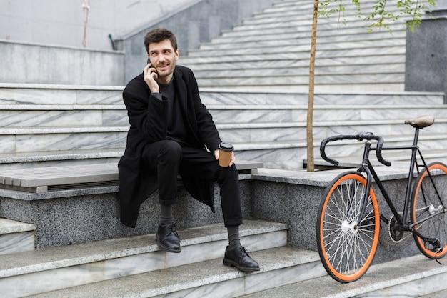 Aantrekkelijke man gekleed in jas zittend op de straat van de stad, praten op de mobiele telefoon, afhaalmaaltijden koffiekopje te houden Premium Foto