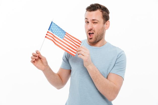 Aantrekkelijke man met borstelharen positief demonstreren kleine amerikaanse vlag en knipogen Gratis Foto