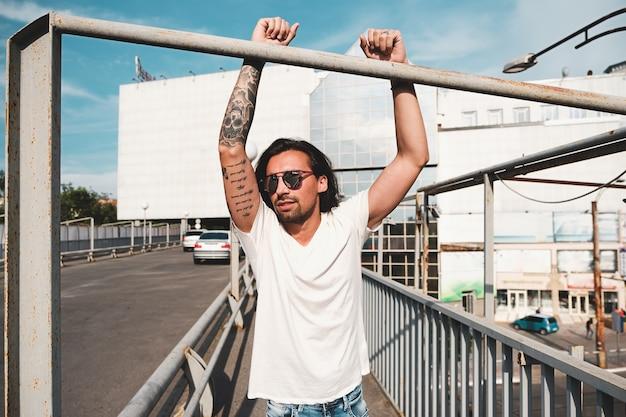 Aantrekkelijke man met zonnebril opknoping uit in de stad Gratis Foto