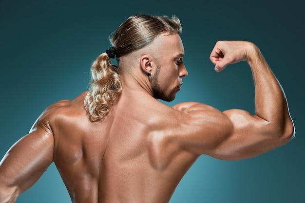 Aantrekkelijke mannelijke lichaamsbouwer op blauwe achtergrond Gratis Foto