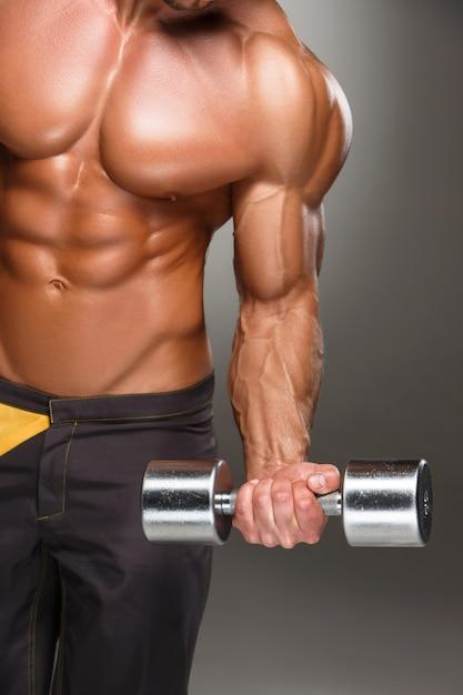 Aantrekkelijke mannelijke lichaamsbouwer op grijze muur Gratis Foto