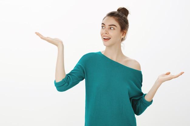 Aantrekkelijke moderne vrouw die een beslissing neemt, keuzes afwegen, de linkerhand opheft met het product of uw logo Gratis Foto