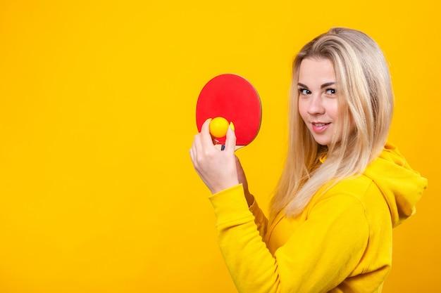 Aantrekkelijke mooie jonge blonde vrouw in casual gele sportieve kleding spelen pingpong, met een bal en racket. Premium Foto